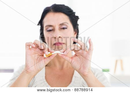 Woman snapping her cigarette on white background