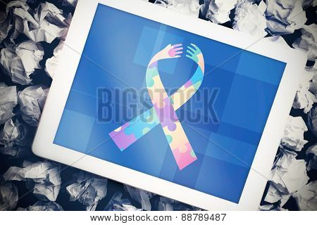 Autism awareness ribbon against tablet pc with blue screen