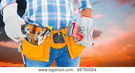 Midsection of handyman holding hand tools against orange and blue sky with clouds