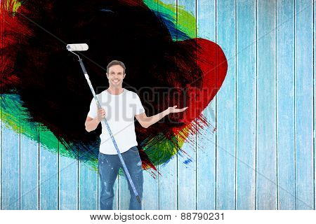 Man gesturing while holding paint roller against wooden planks