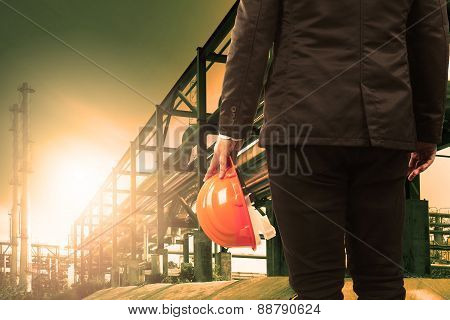 Engineering Man And Safety Helmet Standing Against Beautiful Light Sun Shine In Heavey Petrochemical