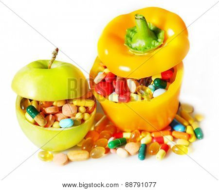 Apple, paprika and colorful pills, on light background