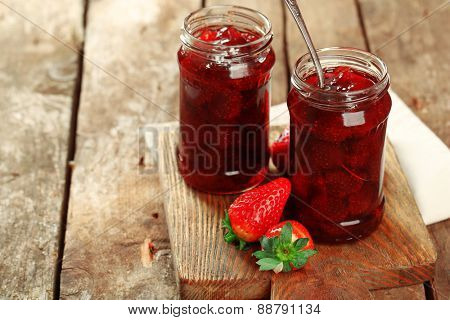 Jars of strawberry jam with berries on wooden background