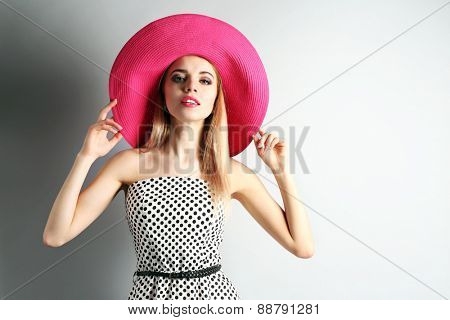 Portrait of young model with pink hat on gray background