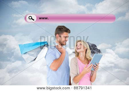 Attractive young couple holding shopping bags looking at tablet pc against mountain peak through the clouds