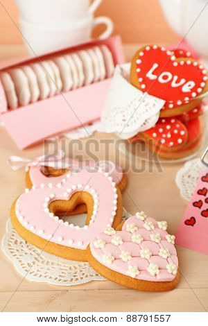 Heart shaped cookies for valentines day and tea bags on wooden background