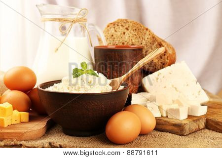 Tasty dairy products with bread on table on light background