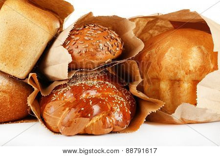 Fresh bread in paper bags on white background