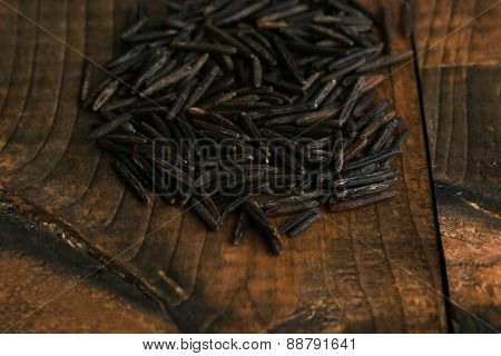 grains of black rice on wooden background