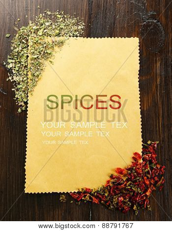 Spices on paper sheet on wooden background
