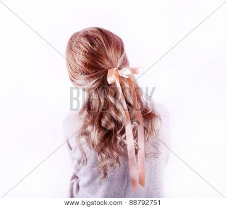 Female hairstyle with color ribbon on white wall background