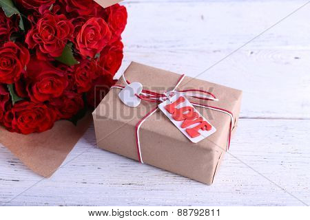 Bouquet of red roses wrapped in paper and present box on wooden background