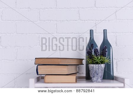 Interior design with plant, glass bottles and stack of books on tabletop on white brick wall background
