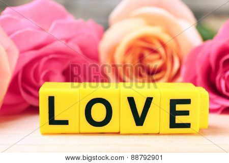 Beautiful roses with word LOVE on wooden table and blurred background