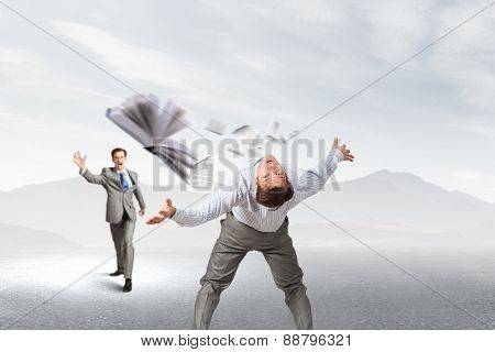 Young businessman trying to evade from thrown book