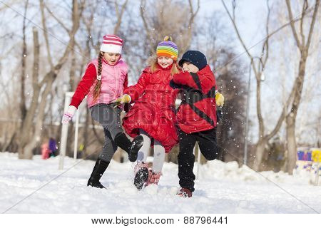 Cute children jumping and having fun in winter park