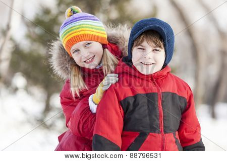 Cute girl and boy having fun in winter park