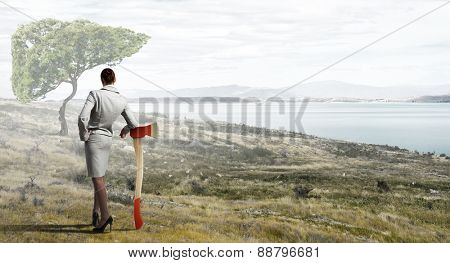 Young businesswoman with axe and green tree