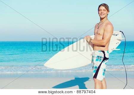 A young surfer with his board on the beach