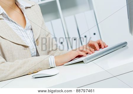 Close up of woman's hands working in office on computer