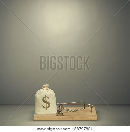 bag with money in wooden mousetrap over dark grey background
