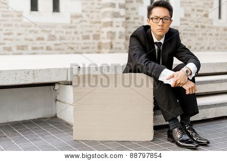 Businessman in a city street sitting next to blank banner