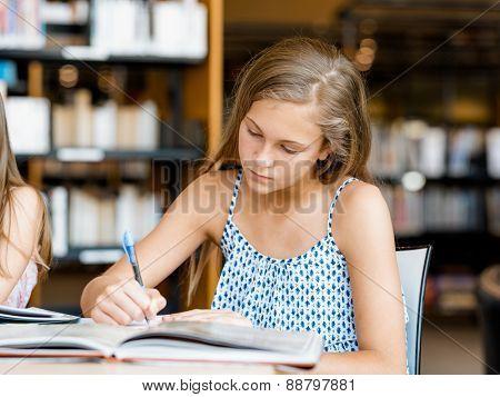 Girl doing her homework in library