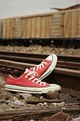stock photo of train track  - Red shoes leaning on the train tracks - JPG