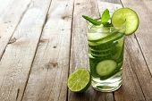 stock photo of cucumbers  - Nutritious detox water with lime and cucumber in a glass against a wood background - JPG
