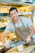 stock photo of deli  - Local deli worker slicing some cheese - JPG