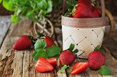 image of food crops  - ripe strawberries and mint leaves on a wooden background - JPG