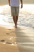 image of footprint  - Backlight of a man legs walking on the beach leaving footprints - JPG