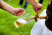 stock photo of draft  - man is tapping a draft beer from a barrel on a wedding - JPG