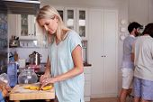 pic of gathering  - young woman carefully cutting fresh lemon at a friends gathering in kitchen at home - JPG