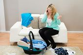 foto of laundry  - Woman Talking On Mobile Phone With Laundry Clothes In Living Room - JPG