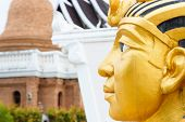 picture of pharaoh  - left side of golden pharaoh statue with pagoda background - JPG