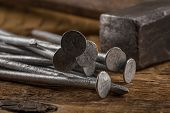 picture of wood craft  - Vintage old hammer with nails on wood table background - JPG