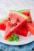 stock photo of watermelon slices  - sliced watermelon with mint leaf on a white plate - JPG