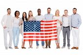 stock photo of bonding  - Full length of happy diverse group of people bonding to each other and holding flag of America while standing against white background together - JPG