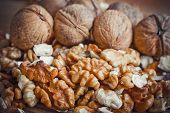 stock photo of walnut  - Walnut kernels and whole walnuts on rustic old wooden table