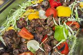 pic of veal  - Pieces of veal tandoori meat with salad on display at an indian restaurant buffet - JPG