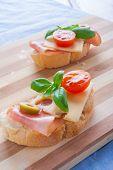 stock photo of smoked ham  - small sandwiches with smoked ham cheese and cherry tomato - JPG