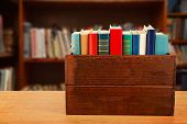 image of wooden crate  - Books in wooden crate on bookshelves background - JPG