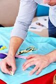 foto of tailoring  - Male dressmaker tailor fabric on table - JPG