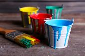 stock photo of bucket  - Metal buckets with colorful paint on wooden background - JPG