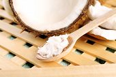 picture of flesh  - Fresh coconut flesh in wooden spoon on wooden grid background - JPG