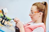 picture of prosthesis  - Female dental technician working with tooth dentures at prosthesis laboratory - JPG