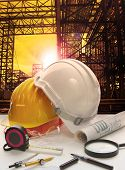 foto of industrial safety  - safety helmet on engineer working table against pipe line structure in heavy petrochemical industry estate - JPG