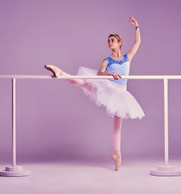 stock photo of ballet barre  - classic ballet dancer in white tutu posing on one leg at ballet barre on a lilac background - JPG