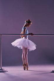 foto of ballet barre  - classic ballet dancer in white tutu at ballet barre on a lilac background - JPG